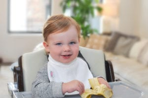 a smiling baby holding a banana at his feeding table wearing a Bibby bib