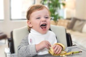 a yelling baby eating a banana at his feeding table wearing a Bibby bib