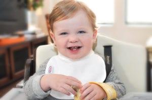 a smiling baby eating a banana at his feeding table wearing a Bibby bib