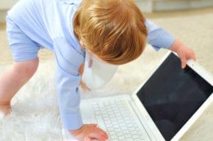 a baby opening a laptop wearing a Bibby bib