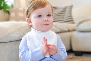 a smiling baby wearing a Bibby bib