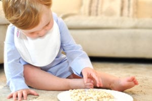 a baby reaching for cheerios wearing a Bibby bib