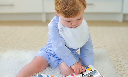 a baby reading a book wearing a Bibby bib