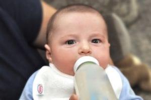 a baby drinking a bottle wearing a Bibby bib