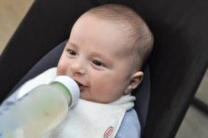 a smiling baby drinking a bottle while wearing a Bibby bib