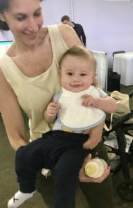 a mother holding a baby who is smiling and wearing a Bibby bib